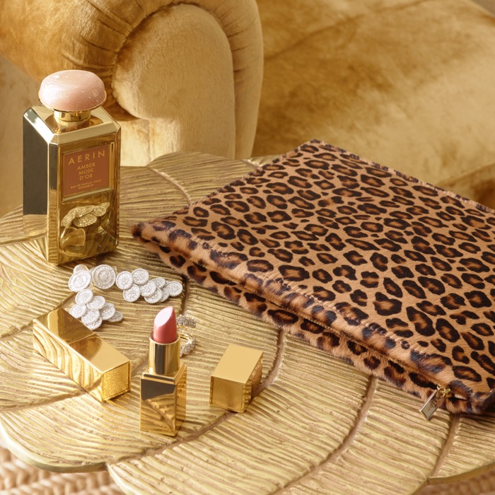An AERIN leopard pouch rests next to a bottle of AERIN Amber Musk D'or Fragrance and an AERIN Rose Balm Lipstick