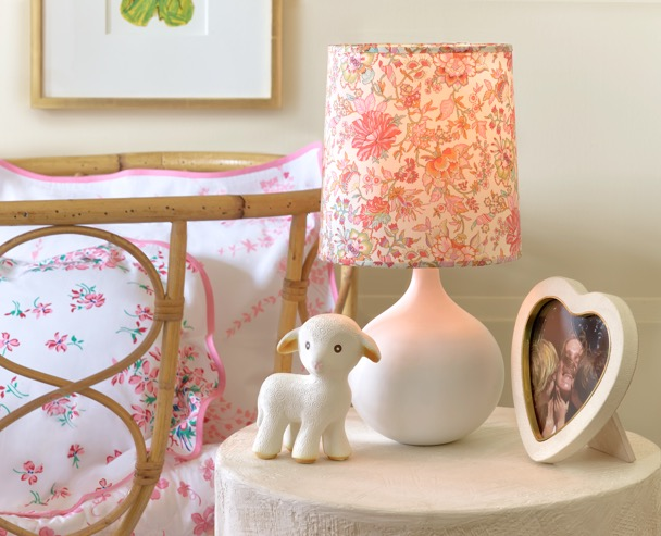 The AERIN Mini Warren Table Lamp in white with the Mini Warren Floral Lamp Shade next to a vintage wicker bassinet