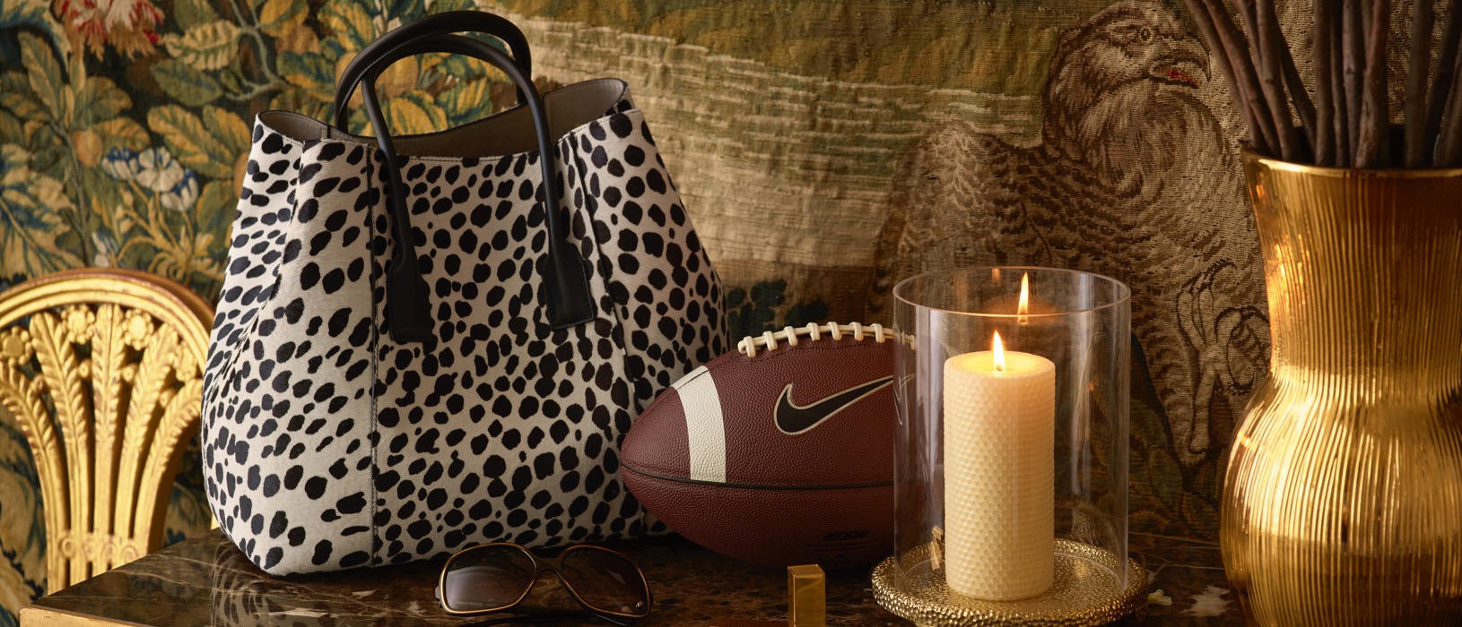 The AERIN Dalmation Mini Weekender resting on a hall table next to a football, Tulln Candle and Rose Balm Lipstick