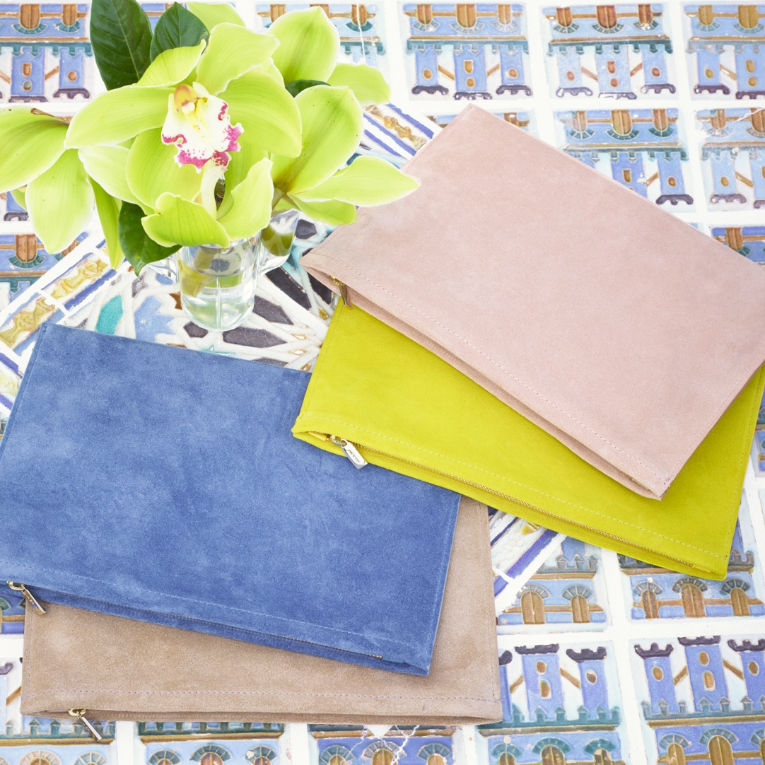An assortment of beautiful AERIN suede pouches that are perfect for summer