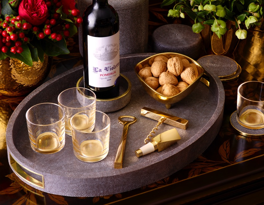 The AERIN Modern Shagreen Tray in chocolate holding crystal glasses, a chocolate shagreen wine coaster, Leon corkscrew, Leon bottle opener and Leon bottle stopper.