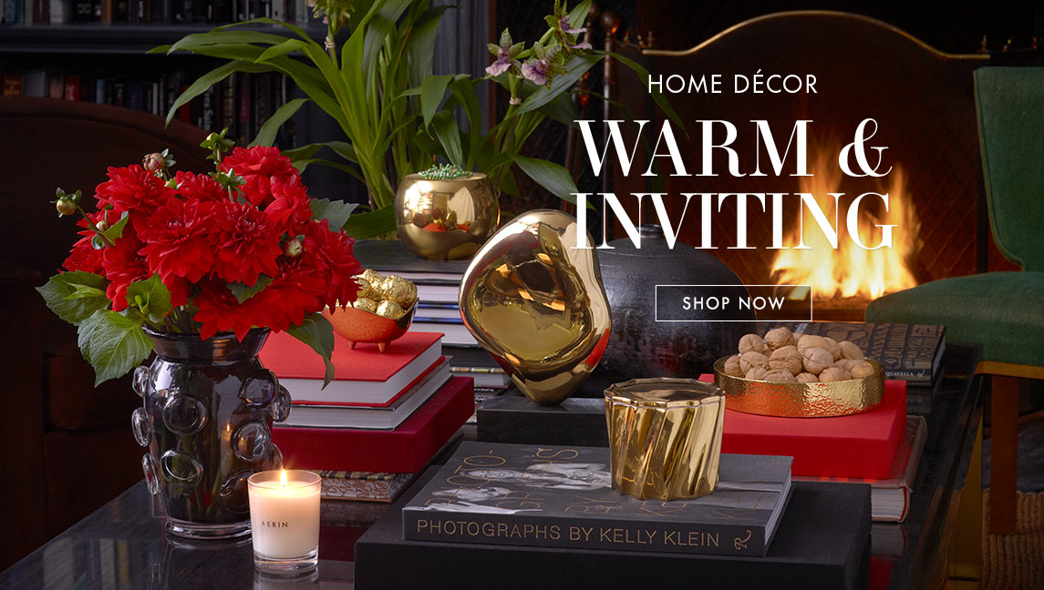 A coffee table strewn with an Abel Vase, AERIN candles, a tulln dish and an oversized match striker