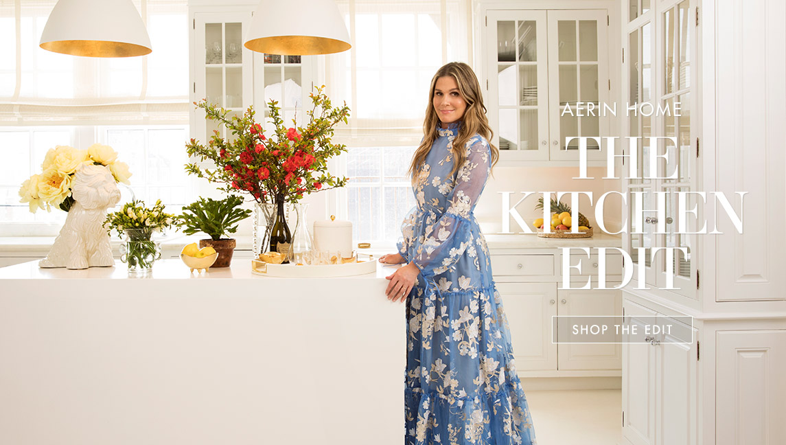 Aerin Lauder stands in a blue dress in her kitchen with some of her picks for essential home décor items.