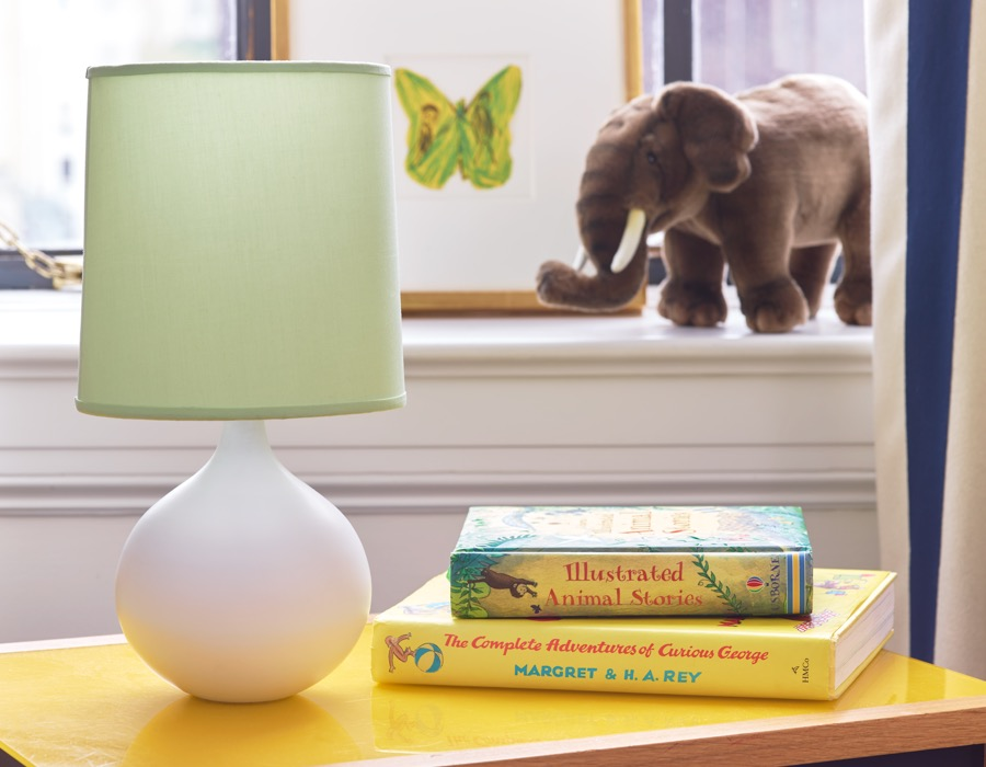 A child's bedside table decorated with the AERIN Mini Warren Table Lamp in white with the Mini Warren Floral Lamp Shade in Seafoam.