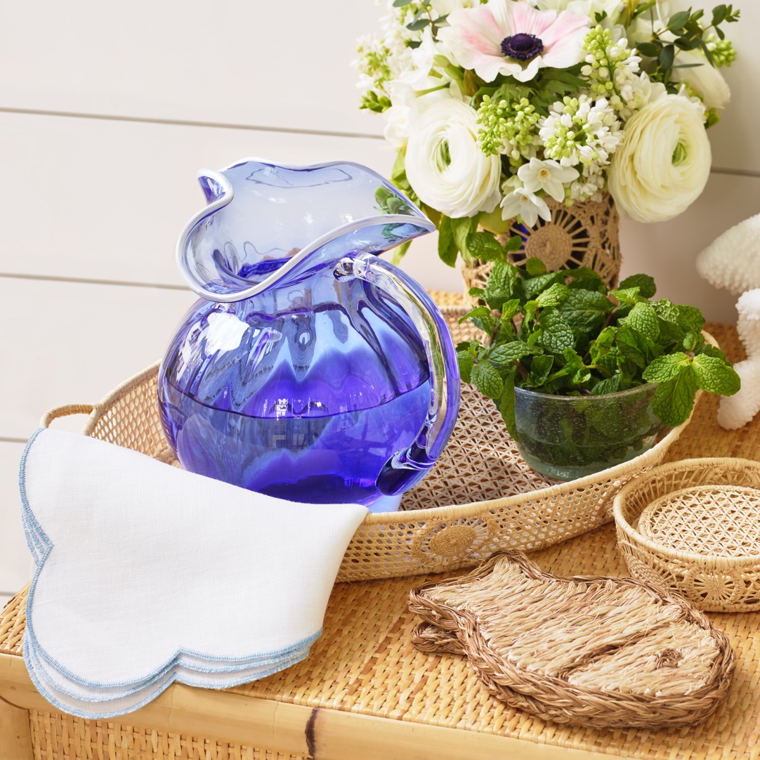 The AERIN carlotta pitcher with the ines nut bowl, embroidered scalloped dinner napkins and fish coaster set