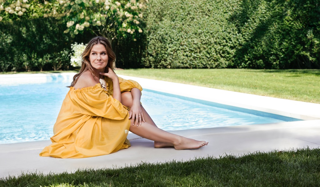 Aerin lounging by the pool in a yellow dress