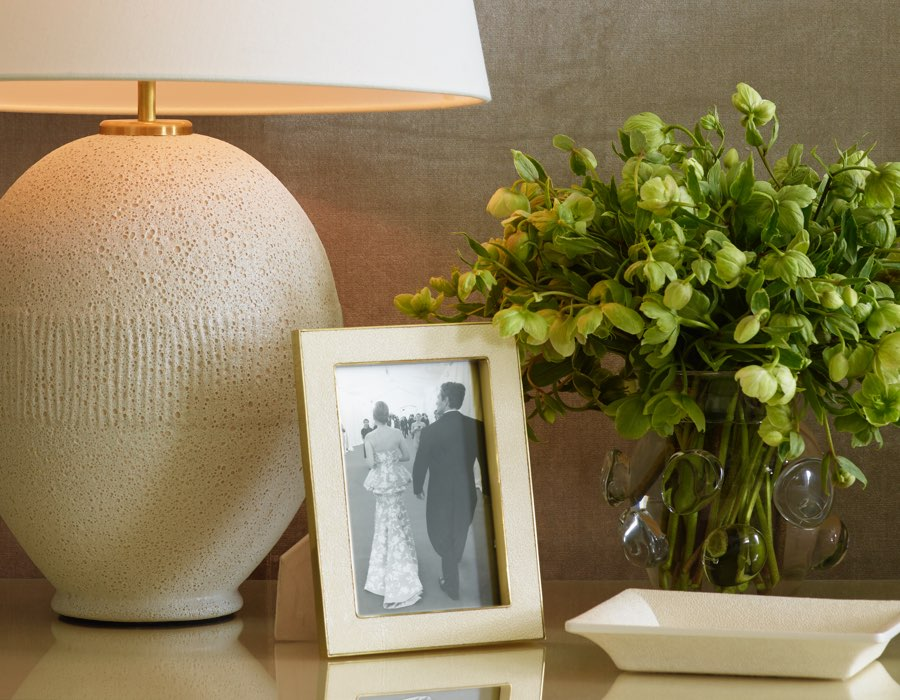 A bedside table with the AERIN Toulon Table Lamp in Volcanic Ivory
