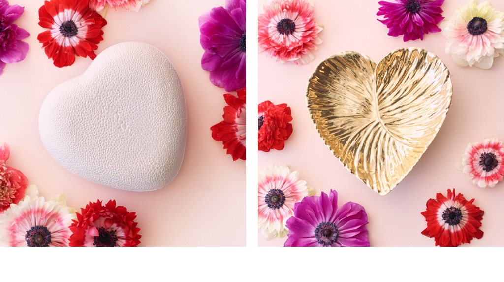 New AERIN Raffia Pouch laying next to the AERIN Heart Raffia Keychain on a pink background with flowers