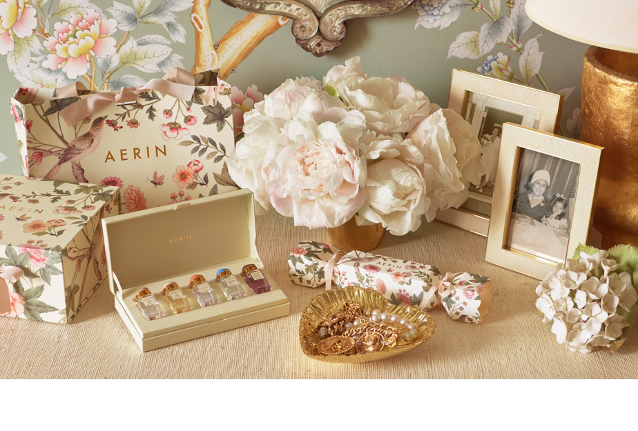 AERIN's Holiday shopping bags, a Fragrance Collection Discovery Set, a gold heart dish and Shagreen frames atop Aerin's dresser