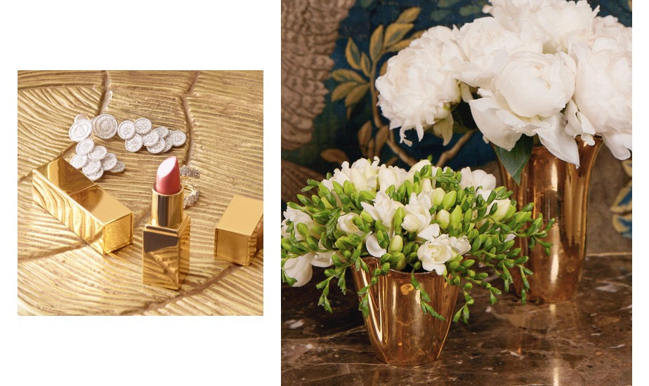 A Rose Balm Lipstick atop a gold table and Gold Clover Vase atop a hall table